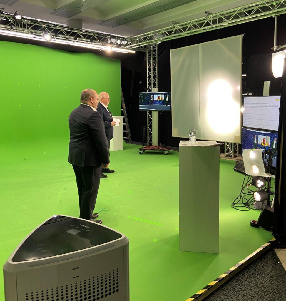 Extrabildschirme ermöglichen den beiden Rednern, während der Veranstaltung das zu verfolgen, was auch das Publikum geboten bekommt.